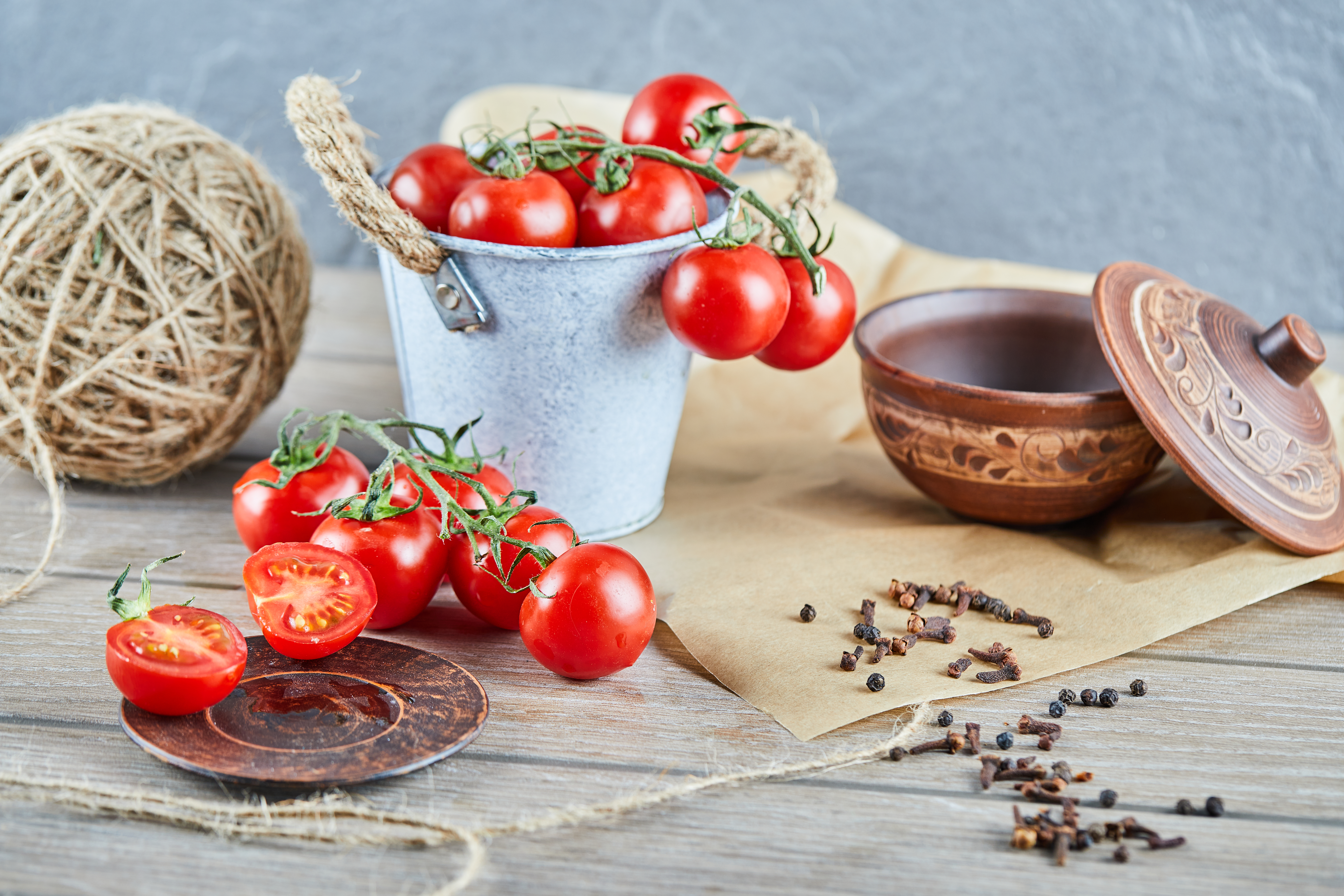 Bucket of tomatoes and half cut tomato on wooden table